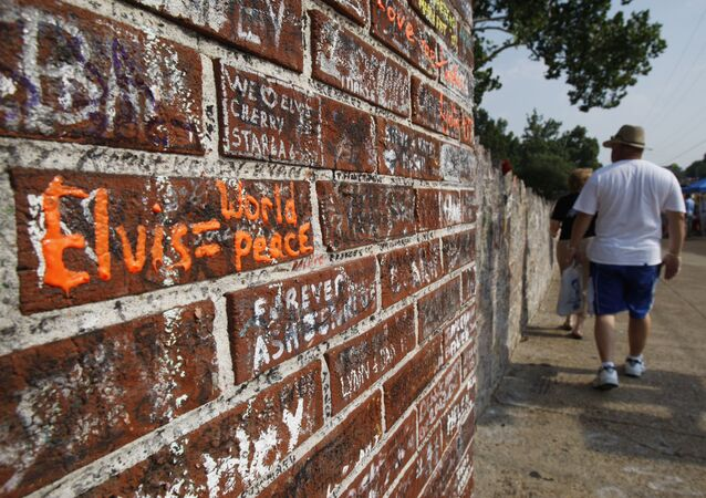 People walk by the wall filled with inscriptions outside the Graceland Mansion, Elvis Presley's home in Memphis, Tennessee, 14 August 2007