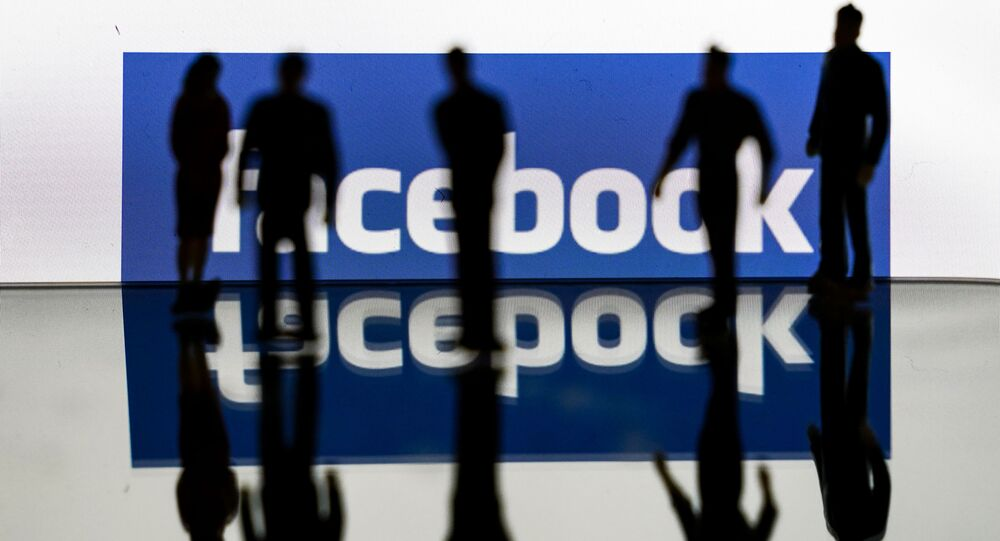 (FILES) In this file photo taken on February 14, 2020 silhouettes are seen in front of the logo of US social media Facebook in Brussels