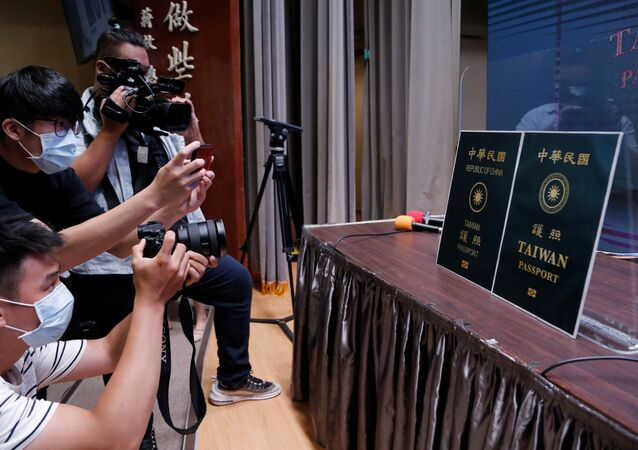 Members of the media take photos of paper cut outs of the old and new (R) Taiwan passport displayed in Taipei, Taiwan, September 2, 2020