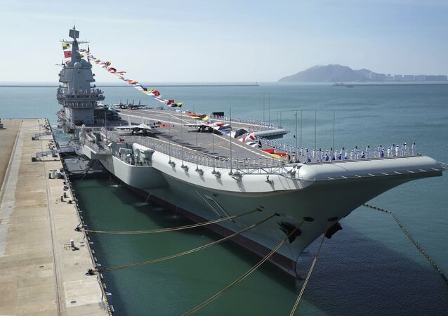 FILE - In this Dec. 17, 2019, file photo provided by Xinhua News Agency, the Shandong aircraft carrier is docked at a naval port in Sanya in southern China's Hainan Province
