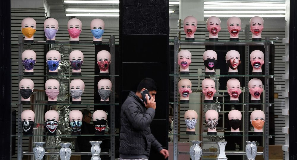 A member of the public walks past a shop selling face masks for the COVID-19 pandemic in Glasgow on September 2, 2020. The Scottish government imposed fresh restrictions on the city after a rise in cases of the novel coronavirus.