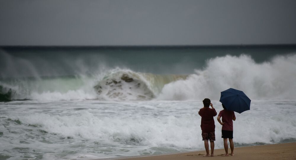 Two men watch the waves during swells brought by the approaching typhoon Maysak on Haeundae beach in Busan on September 2, 2020. - Flights were grounded in South Korea and storm warnings issued on both sides of the Korean peninsula as a typhoon forecast to be one of the most powerful in years made its approach.
