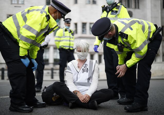 Police officers talk to an activist from the climate protest group Extinction Rebellion who is sat in the road in Parliament Square in central London on September 2, 2020 on the second day of the group's new series of 'mass rebellions'.