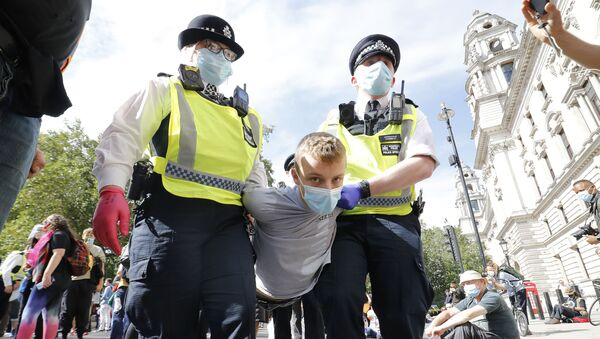 Police officers wearing face masks and gloves due to the COVID-19 pandemic, detain an activist from the climate protest group Extinction Rebellion as they demonstrate in Parliament Square in London on September 2, 2020, on the second day of their new season of mass rebellions. - Sputnik International