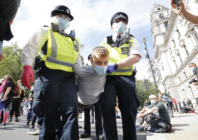 Police officers wearing face masks and gloves due to the COVID-19 pandemic, detain an activist from the climate protest group Extinction Rebellion as they demonstrate in Parliament Square in London on September 2, 2020, on the second day of their new season of mass rebellions.