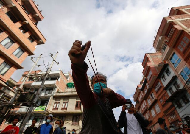 A man uses a slingshot during the protest after locals try to pull the chariot of Rato Machhindranath amid the ban on public and religious gatherings to control the spread of the coronavirus disease (COVID-19) in Lalitpur, Nepal September 3, 2020