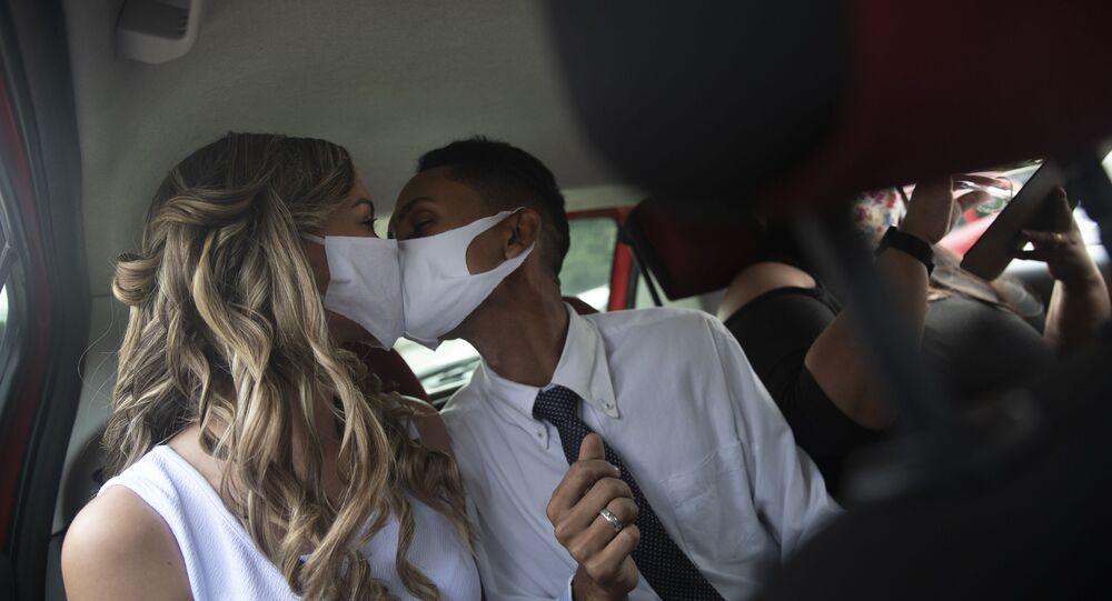 Wearing masks to prevent the spread of the new coronavirus, Thiago do Nascimento, right, and Keilla de Almeida kiss during their drive-thru wedding at the registry office in the neighborhood of Santa Cruz, Rio de Janeiro, Brazil, Thursday, May 28, 2020.