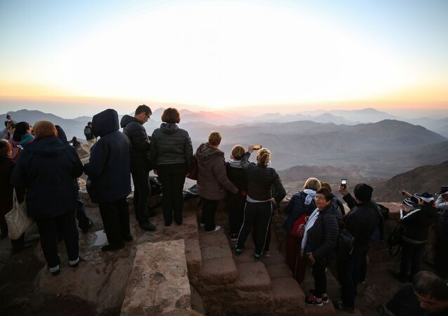 Tourists stand to watch the sunrise after scaling Mount Catherine, above the 6th-century Greek Orthodox Christian monastery of Saint Catherine, near the Egyptian town of the same name in south of the Sinai peninsula, on October 19, 2018, as part of an inter-religious peace conference under slogan Here We pray together.