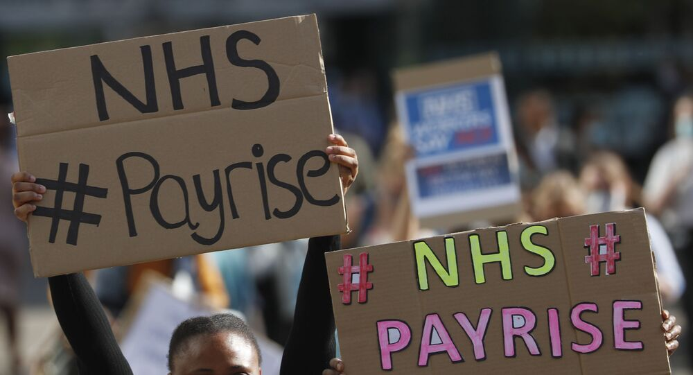 Demonstrators, a number of them nurses and care workers from St Thomas' Hospital, hold placards as they protest for a pay rise in London, Wednesday, 29 July, 2020.