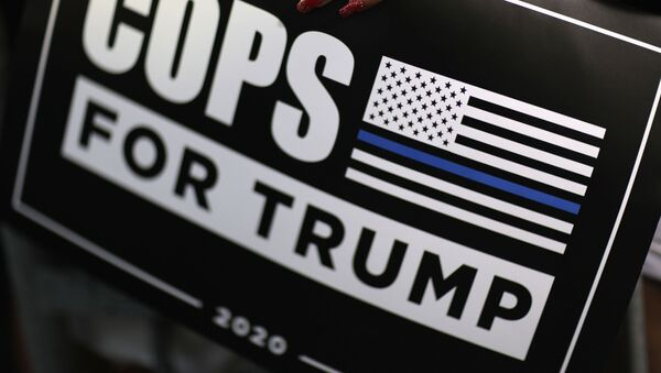 A supporter holds a Cops for Trump sign as U.S. President Donald Trump delivers a campaign speech at Arnold Palmer Regional Airport in Latrobe, Pennsylvania, U.S., September 3, 2020 - Sputnik International