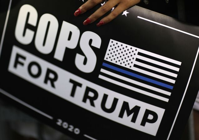 A supporter holds a Cops for Trump sign as U.S. President Donald Trump delivers a campaign speech at Arnold Palmer Regional Airport in Latrobe, Pennsylvania, U.S., September 3, 2020