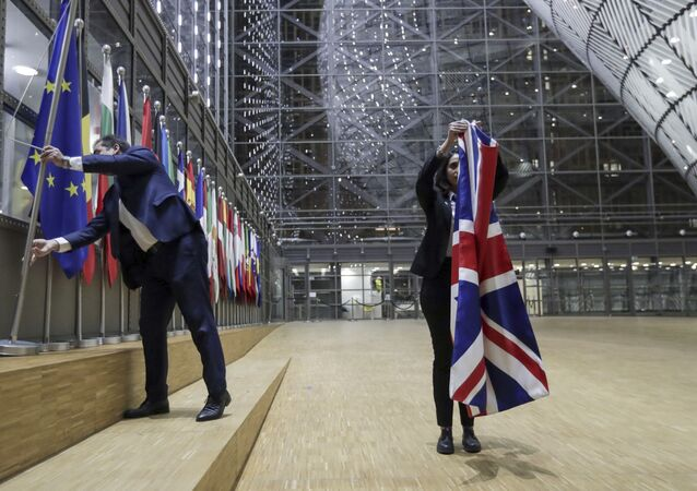 Members of protocol remove the Union flag from the atrium of the Europa building in Brussels, Friday, Jan. 31, 2020