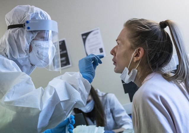 A medical worker, left, performs a COVID-19 test at a test center at Vnukovo airport outside Moscow, Russia, Friday, Aug. 7, 2020. Authorities in Russia say they are about to approve a COVID-19 vaccine, with mass vaccinations planned as early as October 2020, using shots that are yet to complete clinical trials