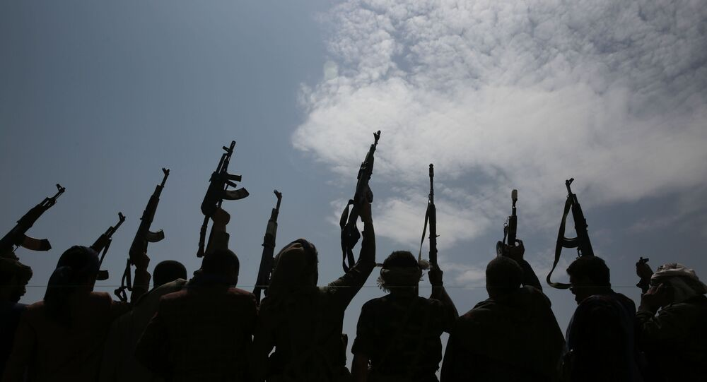 A silhouette of tribesmen loyal to Houthi rebels raise their weapons as they chant slogans during a gathering against the agreement to establish diplomatic relations between Israel and the United Arab Emirates in Sanaa, Yemen, Saturday, Aug. 22, 2020.