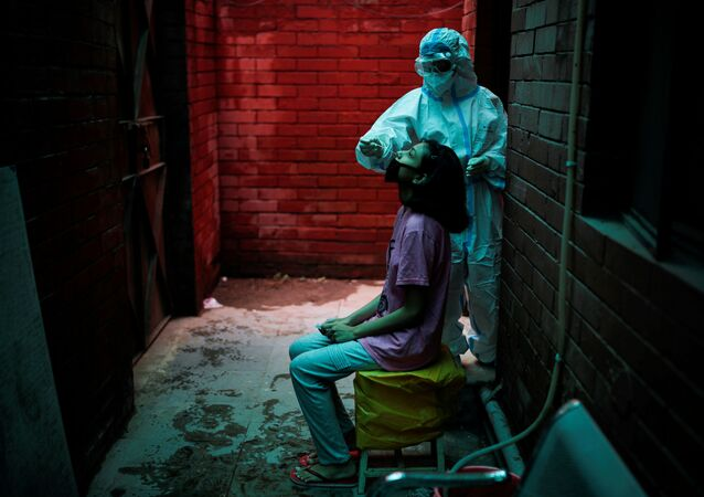 A health worker in personal protective equipment (PPE) collects a sample using a swab from a person at a local health centre to conduct tests for the coronavirus disease (COVID-19), amid the spread of the disease, in New Delhi, India August 31, 2020.