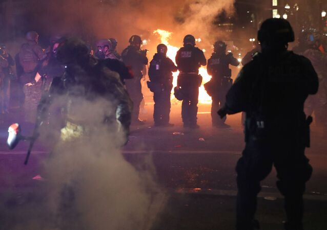 Federal Law Enforcement officers fire teargas and less lethal munitions at protesters during a demonstration against racial inequality and police violence in downtown Portland, Oregon, U.S. July 25, 2020. Picture taken July 25, 2020.