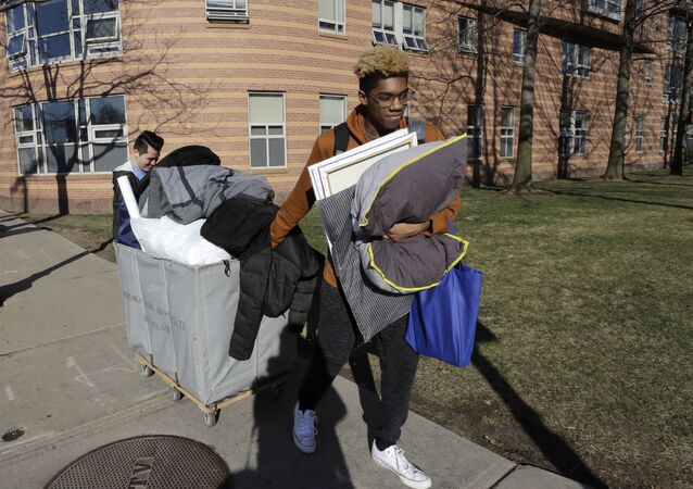 Northeastern University sophomore Philip Thomas, of Hamden, Conn., front, pulls a cart of belongings as he moves out of his residence hall as classmate Jarrett Anderson, of Las Vegas, left, assists him, Sunday, March 15, 2020, in Boston. Students have been asked by the school to move out of residence halls out of concern about the spread of the coronavirus. For most people, the new coronavirus causes only mild or moderate symptoms, such as fever and cough. For some, especially older adults and people with existing health problems, it can cause more severe illness, including pneumonia. The vast majority of people recover from the new virus.
