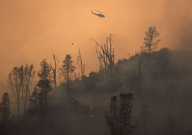 A helicopter and crew releases water to extinguish a section of the LNU Lightning Complex Fire near Middletown, California, U.S. August 24, 2020.