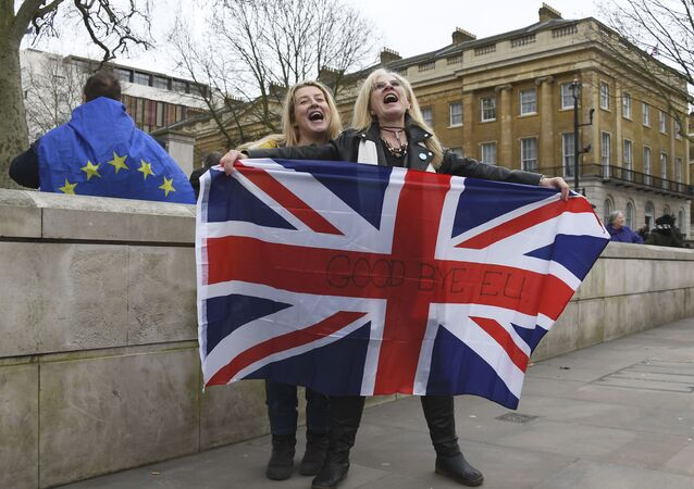 Brexit supporters hold the Union flag with a text reading Goodbye EU as they celebrate next to a person wearing the EU flag in London, Friday, 31 January 2020.