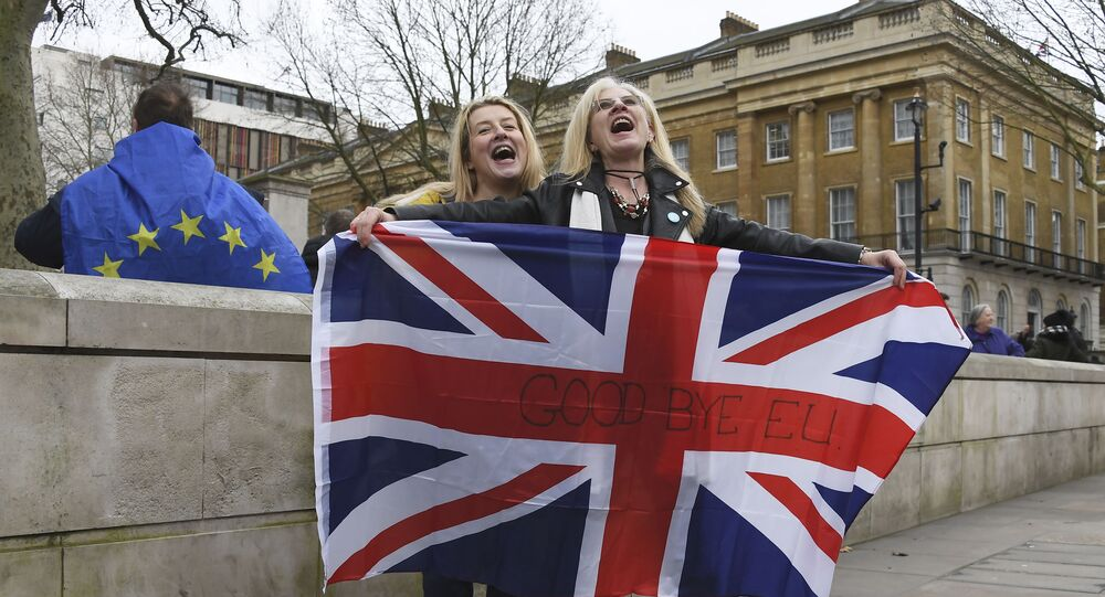 Brexit supporters hold the Union Jack with a text reading Goodbye EU as they celebrate next to a person wearing the EU flag in London, Friday, Jan. 31, 2020