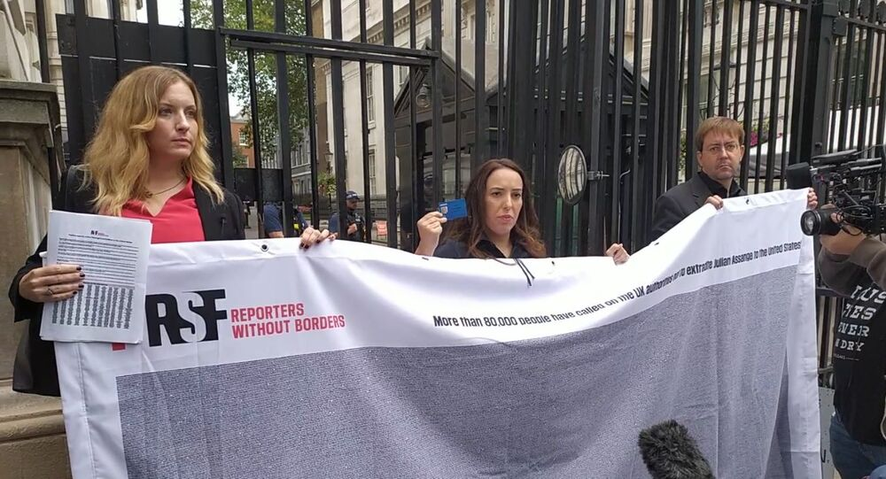 Rebecca Vincent and Stella Moris at Number 10 Downing Street holding up banner with signatures petitioning for Julian Assange on 7 Septemer 2020.