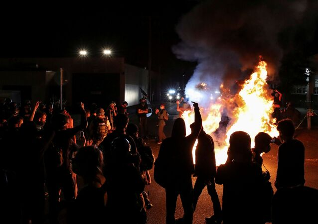 Demonstrators stand near a mattress lit on fire on Martin Luther King Jr. Boulevard outside the Portland Police Bureau's North Precinct on the 101th consecutive night of protests against police violence and racial inequality, in Portland, Oregon, U.S. September 6, 2020