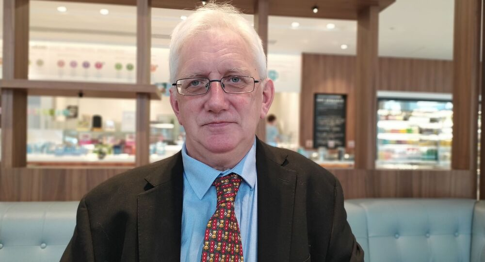 Craig Murray sitting in a cafe near the Old Bailey