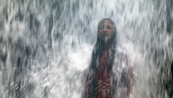 A woman stands under a waterfall as a lake overflows due to heavy rainfall in Mumbai, India August 29, 2020 - Sputnik International