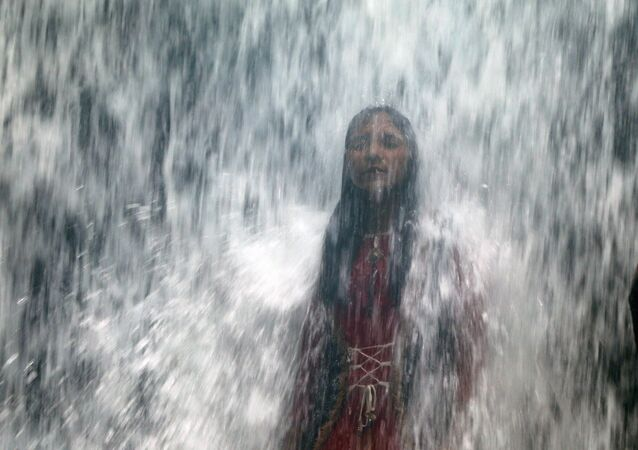 A woman stands under a waterfall as a lake overflows due to heavy rainfall in Mumbai, India August 29, 2020