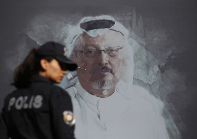 A Turkish police officer walks past a picture of slain Saudi journalist Jamal Khashoggi prior to a ceremony, near the Saudi Arabia consulate in Istanbul, marking the one-year anniversary of his death, Wednesday, Oct. 2, 2019