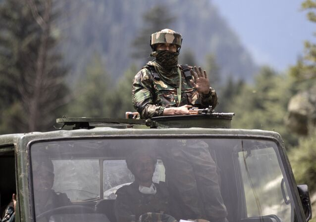 An Indian army soldier keeps guard on top of his vehicle as their convoy moves on the Srinagar- Ladakh highway at Gagangeer, northeast of Srinagar, Indian-controlled Kashmir, 1 September 2020
