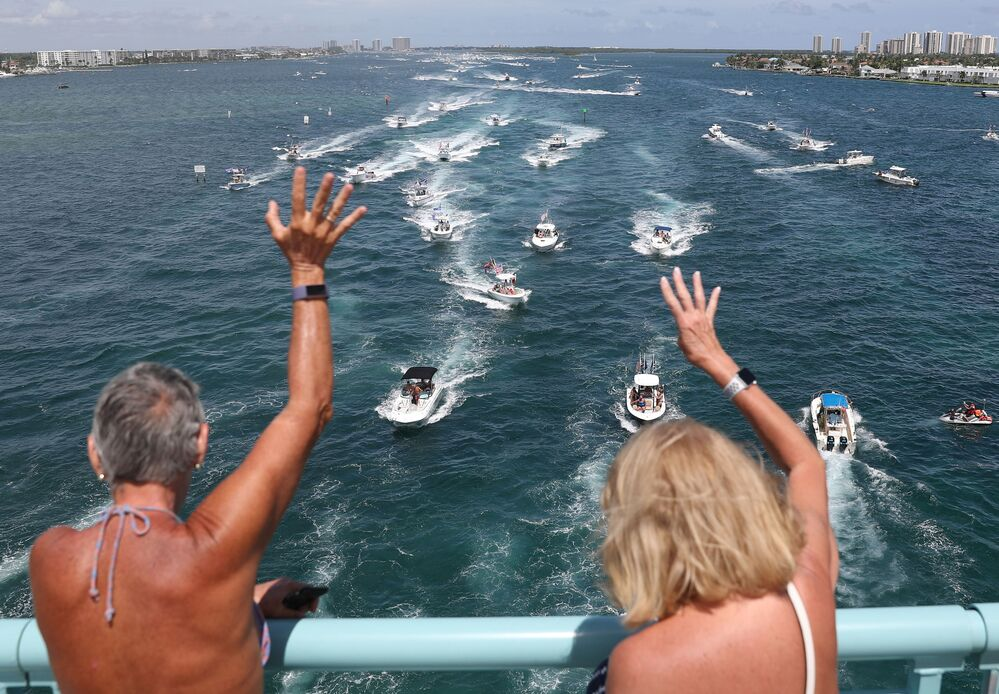 People wave as boaters show their support for President Donald Trump during a parade down the Intracoastal Waterway to just off the shore of President Trump's home at Mar-a-Lago on September 07, 2020 in West Palm Beach, Florida.
