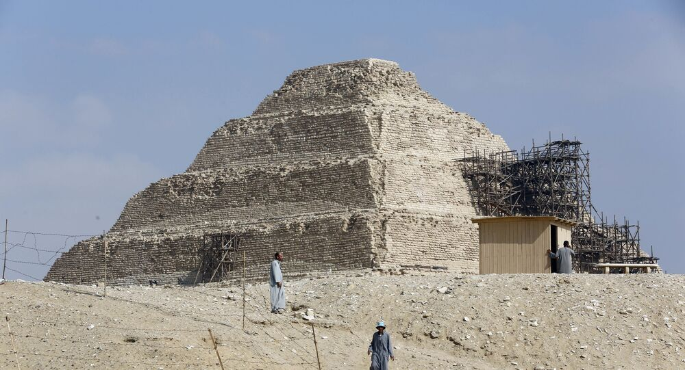 Excavation workers walk in front of the step pyramid of Saqqara, in Giza,14 July 2018.  (AP Photo/Amr Nabil)