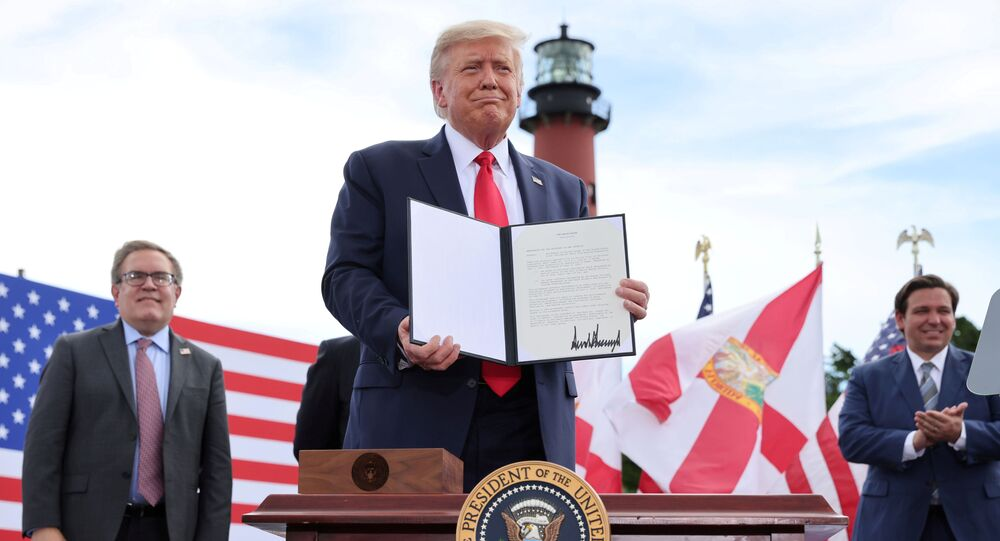 U.S. President Donald Trump stands after signing an extension of the ban on offshore drilling off the coast of the state of Florida in front of a crowd of Trump supporters as U.S. Environmental Protection Agency Director Andrew Wheeler and Florida Governor Ron DeSantis look on in Jupiter, Florida, U.S. September 8, 2020.