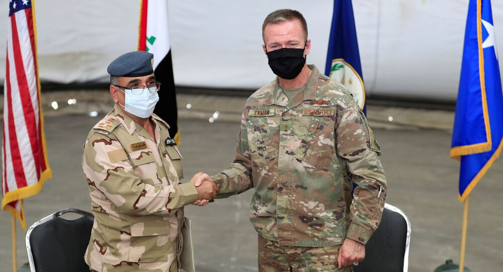 Maj. Gen. Kenneth P. Ekman, Deputy Commander of the Combined Joint Task Force-Operation Inherent Resolve, shakes hand with Brigadier General Salah Abdullah during the ceremonial handover of the Taji military base from US-led coalition troops to Iraqi security forces, at a base north of Baghdad, Iraq, 23 August 2020