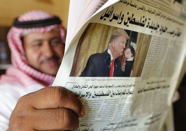 A man holds the daily Asharq Al-Awsat newspaper fronted by a picture of President Donald Trump, at a coffee shop in Jiddah, Saudi Arabia, Wednesday, Jan. 29, 2020