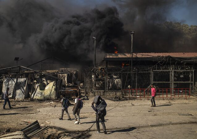 People walk past a fire raging in the camp of Moria on the island of Lesbos after a major fire broke out, on September 9, 2020.