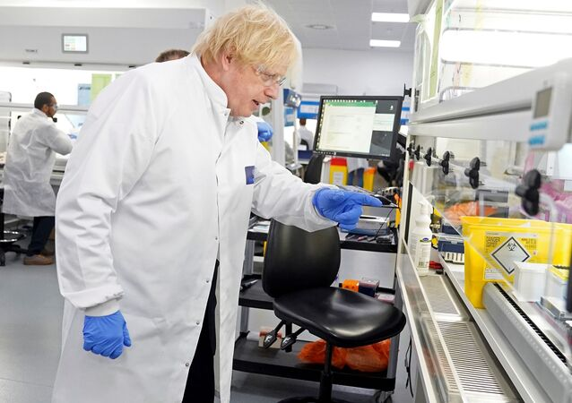 A handout image released by 10 Downing Street, shows Britain's Prime Minister Boris Johnson wearing PPE (personal protective equipment), including eye protection and gloves, during his visit to the UK Biocentre in Milton Keynes, north of London, on June 12, 2020, being used as a Lighthouse Lab facility dedicated to the testing for COVID-19.