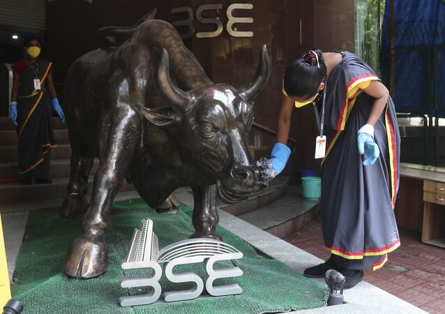 A woman cleans a bronze statue of a bull outside the Bombay Stock Exchange (BSE) in Mumbai, India, Friday, June 12, 2020