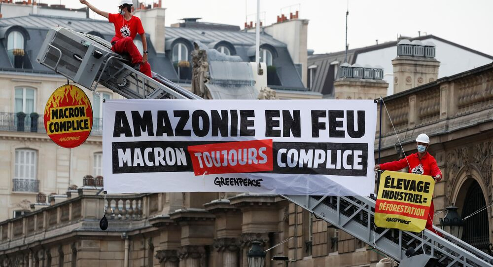 Greenpeace activists stand on a fire truck during an action in front of the Elysee Palace to protest against the ongoing damage to the Amazon rain forest, in Paris, France, September 10, 2020. The slogan reads Amazon on fire. Macron still complicit.