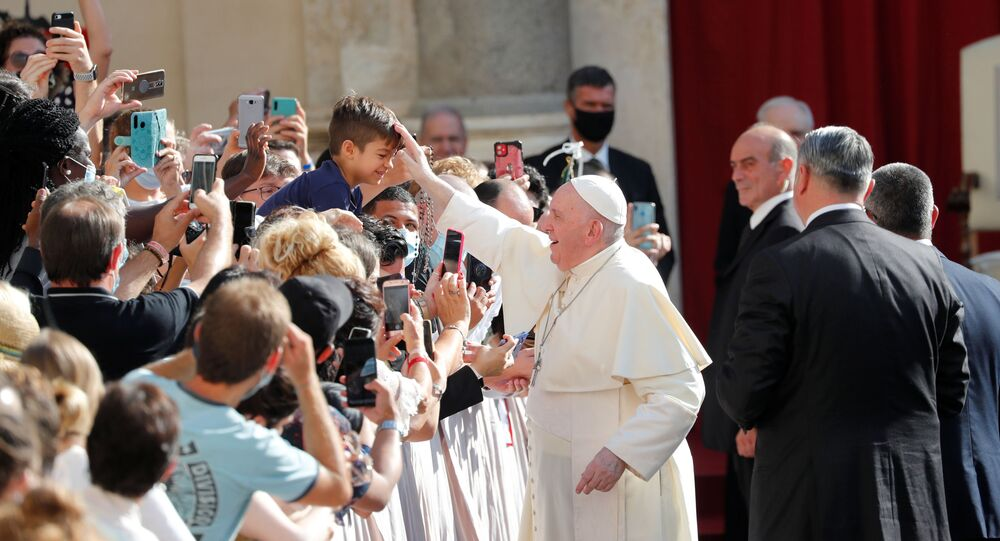 Pope Francis blesses a child as he arrives at the San Damaso courtyard for the weekly general audience at the Vatican, September 9, 2020