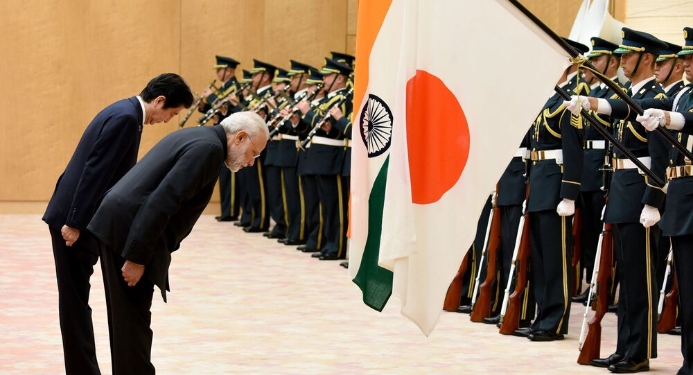 India's Prime Minister Narendra Modi (R) and his Japanese counterpart Shinzo Abe bow to national flags as they review an honor guard before their meeting at Abe's official residence in Tokyo on November 11, 2016