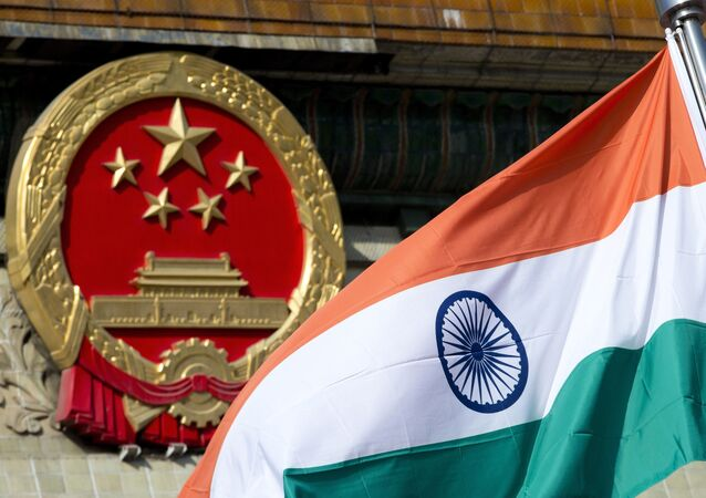 In this Oct. 23, 2013, file photo, an Indian national flag is flown next to the Chinese national emblem outside the Great Hall of the People in Beijing. China's Commerce Ministry said Thursday, Aug. 13, 2020 it has extended punitive tariffs on Indian optical fiber products for five years. The announcement follows a yearlong review after a previous tariff expired in 2019