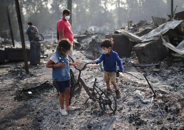 Ashley, 3, and Ethan, 2, look at a burned bicycle after wildfires destroyed a neighbourhood in Bear Creek, Phoenix, Oregon, U.S., September 10, 2020.