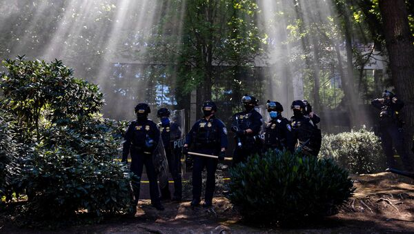 Portland Police officers observe as groups like the Proud Boys and Patriot Prayer faced off against protesters against systemic racism and police brutality in Portland, Oregon, 22 August 2020 - Sputnik International
