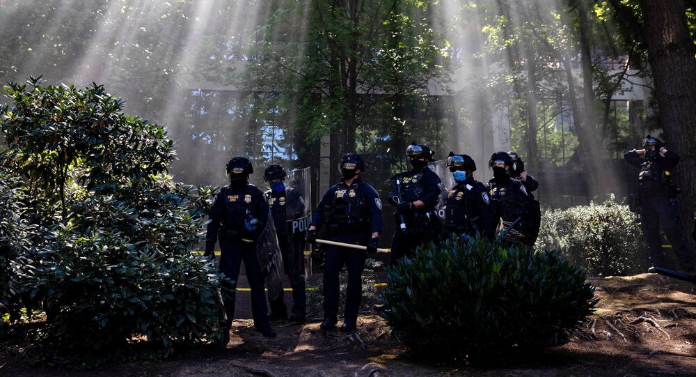 Portland Police officers observe as groups like the Proud Boys and Patriot Prayer faced off against protesters against systemic racism and police brutality in Portland, Oregon, U.S., August 22, 2020