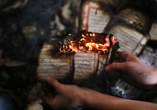 A Palestinian man displays a copy of Islam's holy book, the Koran, still burning inside a mosque that was set ablaze by Israeli settlers in al-Mughayir, in the occupied West Bank near the Jewish settlement of Shilo, on November 12, 2014.