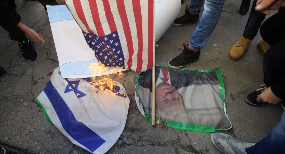 Lebanese and Palestinians students, burn a picture of U S. President Donald Trump, an American flag and an Israeli flag, as they take part in a protest at the Lebanese University, in the southern port city of Sidon, Lebanon, Thursday, Dec. 7, 2017, against U.S. President Donald Trump's decisions to recognize Jerusalem as the capital of Israel.