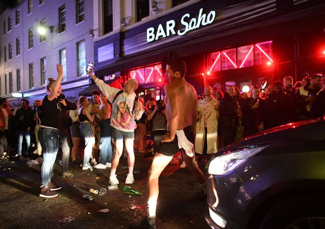 A car tries to drive down a street filled with revellers drinking in London's Soho neighbourhood on 4 July 2020, after the police re-opened the road at 23:00 as COVID-19 pandemic-related restrictions were eased.