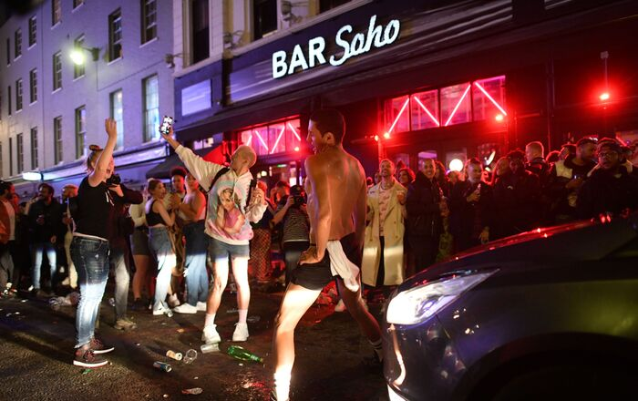 A car tries to drive along a street filled with revellers drinking in the Soho area of London on 4 July 2020, after the police re-opened the road at 23:00 as COVID-19 restrictions were eased over the summer.